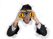 Shocked businessman with binoculars. Shocked businessman breaking through a paper wall looking through binoculars with dollar sign on the lens Royalty Free Stock Image