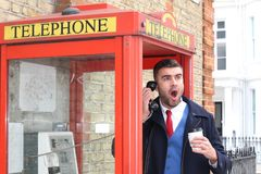Shocked businessman calling by public phone.  Royalty Free Stock Photos