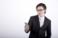 Shocked Businessman with a cellphone. Asian businessman holding a mobile phone looking shocked Stock Photo