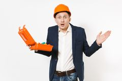 Shocked businessman in dark suit, protective hardhat holding opened case with instruments or toolbox and spreading hands. Isolated on white background. Male royalty free stock photography