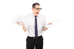 Shocked businessman holding shredded documents Stock Images