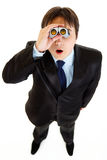Shocked businessman looking through binoculars. Shocked young businessman looking through binoculars isolated on white Royalty Free Stock Images