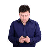 Shocked businessman looking at cell phone against white backgrou Royalty Free Stock Photography