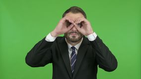 Shocked businessman looking from hand binoculars against chroma key. The shocked businessman looking from hand binoculars against chroma key stock footage