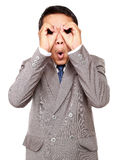 Shocked businessman looking through his circled fingers Stock Photography