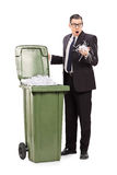 Shocked businessman looking into a trash can Royalty Free Stock Photography