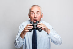 Shocked businessman. Searching with binoculars and looking surprised Royalty Free Stock Photography