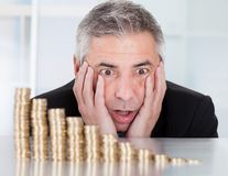 Shocked businessman with stack of coins. Shocked Mature Businessman Looking At Descending Stack Of Coins Stock Image