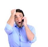 Shocked businessman talking on phone Royalty Free Stock Image