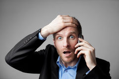 Shocked businessman talking on the phone Stock Photos