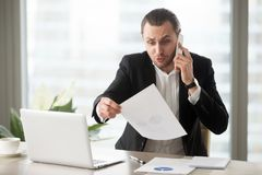 Shocked businessman talks on the phone holding financial report stock photos