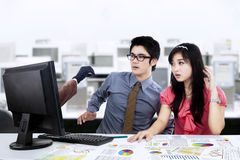 Shocked businesspeople looking hacker. Two young business people shocked of hacker's hand on the screen Stock Photography