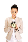 Shocked businesswoman with alarm clock. Stock Photos