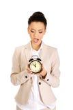 Shocked businesswoman with alarm clock. Stock Photos