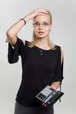 Shocked businesswoman with calculator. Isolated in studio stock image