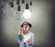 Shocked businesswoman with digital tablet and glowing light bulb. Shocked businesswoman holding digital tablet and looking at glowing light bulb Royalty Free Stock Photo