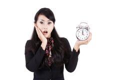 Shocked businesswoman holding alarm clock Royalty Free Stock Images