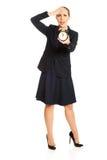 Shocked businesswoman holding alarm clock Stock Photo