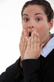Shocked businesswoman. Holding hands to her mouth Stock Photo