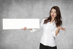 Shocked businesswoman holds a place for your advertisement Stock Photography