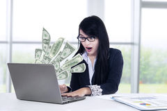 Shocked businesswoman looking money at laptop. Young businesswoman with laptop and money in great online business Stock Photography