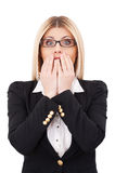 Shocked businesswoman. Shocked mature businesswoman covering mouth with hands and looking at camera while standing isolated on white Royalty Free Stock Images