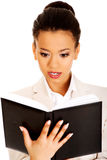 Shocked businesswoman with a notebook. Shocked african businesswoman with a notebook Stock Image