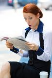 Shocked businesswoman reading newspaper Royalty Free Stock Photography