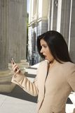 Shocked businesswoman at smartphone Stock Images