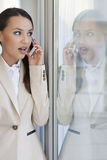Shocked businesswoman using cell phone in office Royalty Free Stock Image