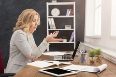 Shocked businesswoman working on laptop at office. Shocked businesswoman working on laptop and having problems, woman sitting at her working place, copy space Stock Image