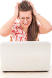 Shocked casual woman looking at laptop because mistake stock photography