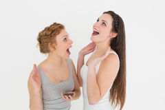 Shocked casual young female friends with mobile phone Stock Photography