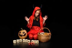 Shocked child in costume of devil. Shocked child in halloween costume of devil with jack o lantern and sweets in basket, isolated on black Royalty Free Stock Photography