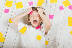 Shocked child with empty stickers on his body. Stress from studying, doing homework Royalty Free Stock Photography