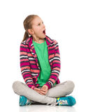 Shocked Child Girl Looking Away. Shocked blond girl in striped fleece blouse, jeans and sneakers sitting on floor with legs crossed and looking away. Full length Royalty Free Stock Images
