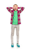 Shocked Child Girl. Girl in striped fleece jacket, jeans and sneakers standing, holding head in hands, looking at camera and shouting. Full length studio shot Royalty Free Stock Photography