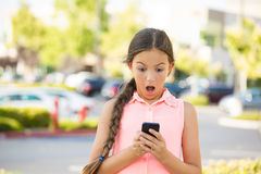 Shocked child texting on mobile, smart phone. Portrait child, surprised girl texting on mobile, using smart phone, isolated outdoors, outside background. Funny Royalty Free Stock Photo