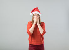 Shocked christmas woman. Wearing a santa hat  over a gray background Royalty Free Stock Photo