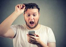 Shocked chubby man watching news on phone royalty free stock photography