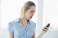 Shocked classy businesswoman using her smartphone Stock Photo