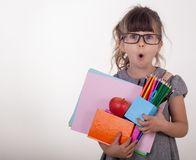 Shocked clever child in eyeglasses holding school supplies. Back to school concept. royalty free stock photo
