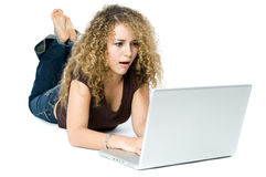 Shocked on the computer. A beautiful young women on a laptop computer looking shocked Stock Image