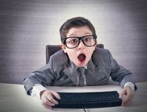 Shocked computer nerd. Shocked child nerd working with a computer Royalty Free Stock Images