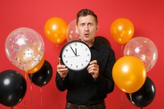 Shocked concerned young man in black classic shirt holding round clock on bright red background air balloons. Time is royalty free stock images