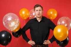 Shocked concerned young man in classic shirt standing with arms akimbo on red background air balloons. St. Valentine`s. International Women`s Day, Happy New royalty free stock photos
