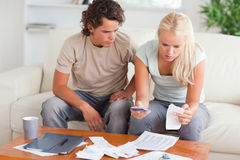 Shocked couple calculating their expenses Stock Photos