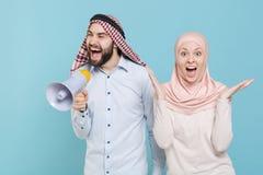 Shocked couple friends arabian muslim man wonam in keffiyeh kafiya ring igal agal hijab clothes isolated on blue