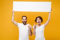 Shocked couple friends bearded guy girl in white t-shirts isolated on yellow orange background. People lifestyle concept
