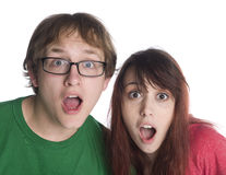 Shocked Couple with Mouth Open Looking at Camera. Close up Shocked Young Couple with Mouth and Eyes Wide Open Looking at Camera, Isolated on White Background Royalty Free Stock Photos